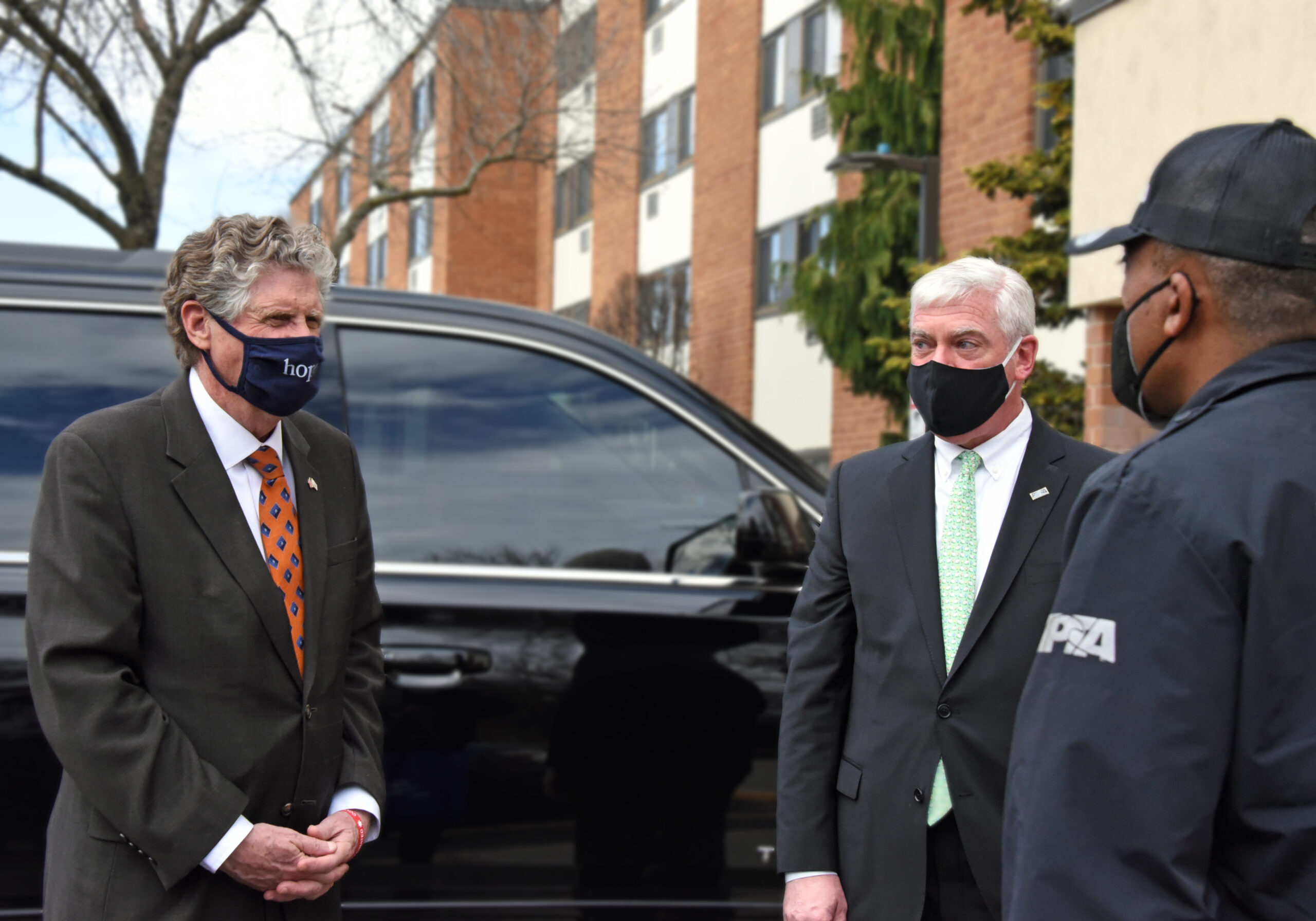 Gov. Dan McKee (l), RIPTA CEO Scott Avedisian (center), and RIPTA driver Jesus Castro (r) outside D'Evan Manor on Cranston Street where RIPTA was delivering a hot lunch to a resident for Meals one Wheels of Rhode Island.